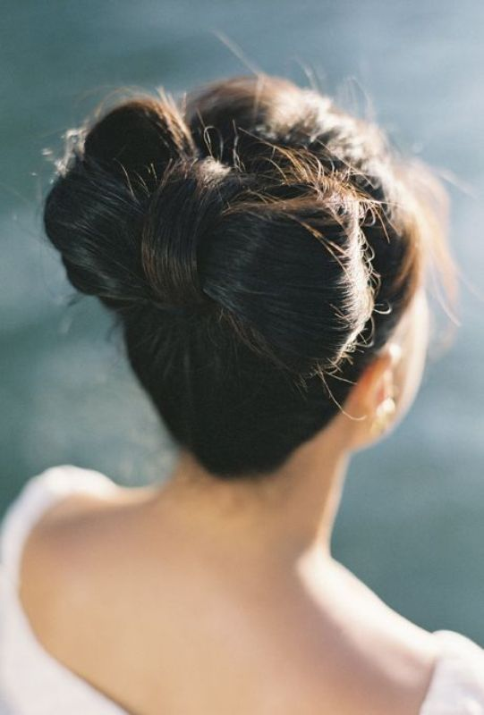 a unique and quirky wedding updo   a large bow with some volume on top and a fringe is a fun and cool idea