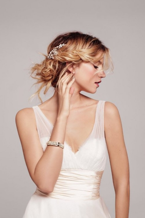 a messy wedding updo with a braided halo and a pearl hairpiece is a lovely and chic idea to rock