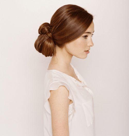 a low updo with a twisted bun and a sleek top is a bold and modern idea for a modern bride with long hair
