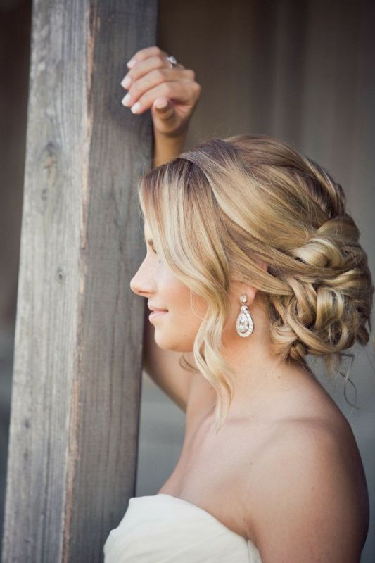a wavy twisted low chignon with some locks down is a beautiful solution that matches many looks