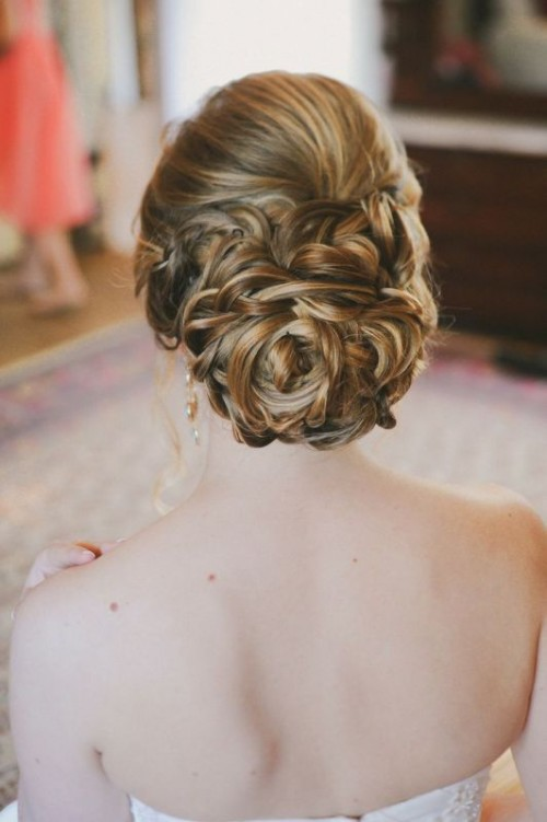 a braided and twisted low bun with a volume on top is a stylish and romantic solution for a modern romantic bride