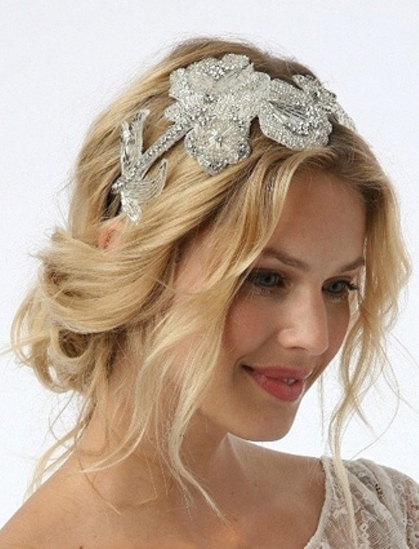 a messy and wavy low updo with some locks down and with an embellished headpiece is a gorgeous option for a bride who loves effortless chic