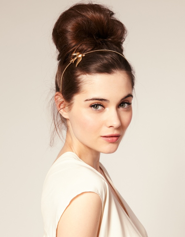 a creative looking top knot with some volume on top and a headpiece with a bird is a stylish and bold option to rock