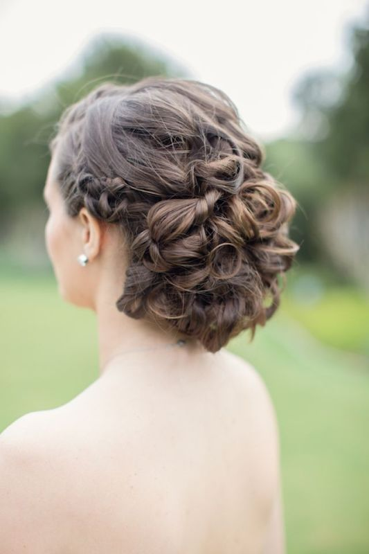 a twisted and curly wedding updo with a complicated and layered top and a braided halo for brides with long and extra long hair