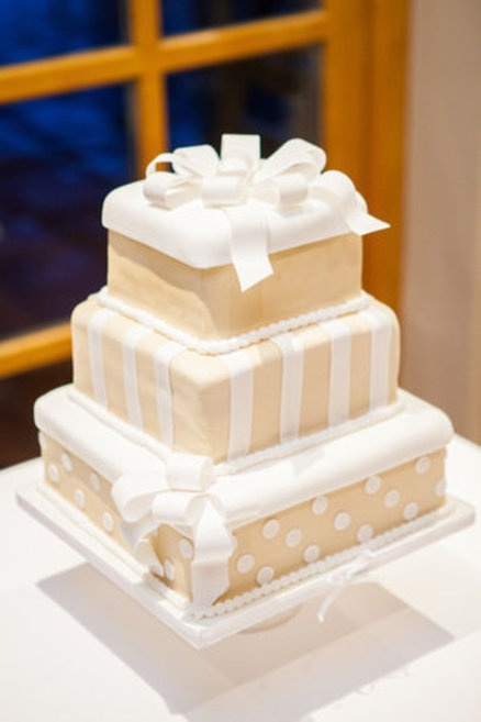 a tan and white Christmas wedding cake composed of gift boxes stacked on each other looks very whimsical
