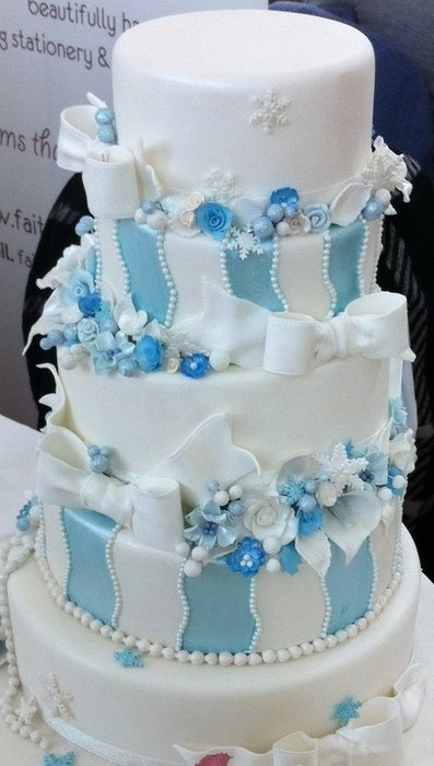 a blue and white Christmas wedding cake decorated with stripes, blooms  and large white bows looks frozen and very pretty