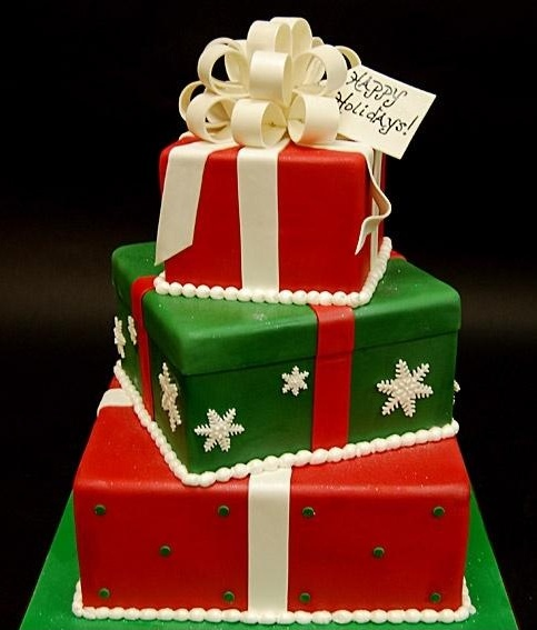 a red, green and white Christmas wedding cake composed of gift boxes, with large bows and a tag is a pretty idea