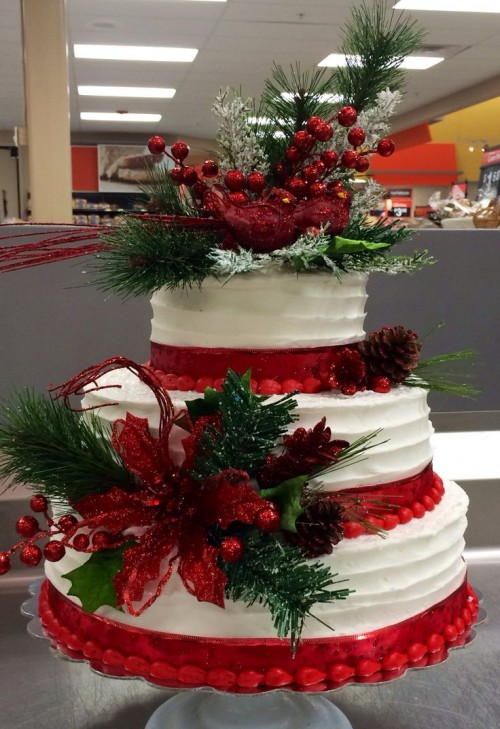 a Christmas wedding cake decorated with red ribbons, cranberries, pinecones, faux greenery and blooms is a cozy rustic piece