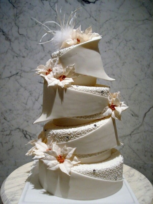 a refined white Christmas wedding cake of sculptural tiers, patterned tiers and with sugar blooms and feathers is a statement