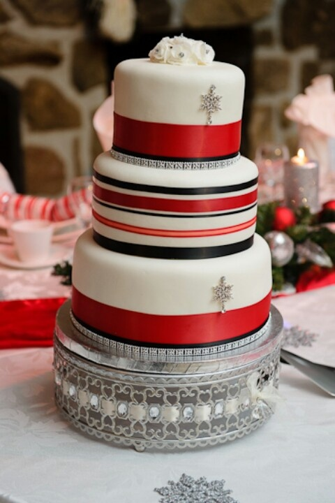 a red, black and white striped Christmas wedding cake decorated with silver snowflakes is a pretty and cozy dessert to rock