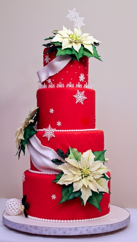 a red Christmas wedding cake with textural tiers, white ribbons and snowflakes plus sugar poinsettia blooms for a traditional Christmas feel