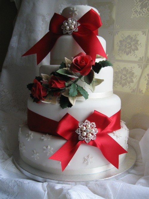 a white wedding cake with a snowflake tier, red ribbon bows with embellishments, greenery and faux roses is a pretty and bold dessert