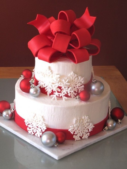 a white Christmas wedding cake decorated with red and silver ornaments, white snowflakes and with a large red bow on top looks very holiday-like