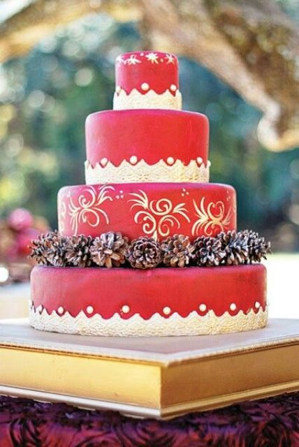 a red Christmas wedding cake with a patterned tier and paintings on it, with pinecones is a pretty and bold dessert