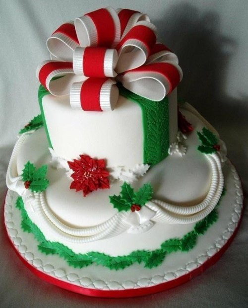 a unique and bold Christmas wedding cake in white, red and green, with colorful leaves, berries and a large bow on top
