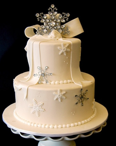 a white Christmas wedding cake, with a large bow on top, snowflakes and rhinestones is a pretty piece