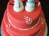 a red Christmas wedding cake with snowballs and funny snowmen toppers is all about winter