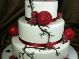 a white Christmas wedding cake with red ribbons, branches, frozen ornaments and berries is a unique idea for Christmas