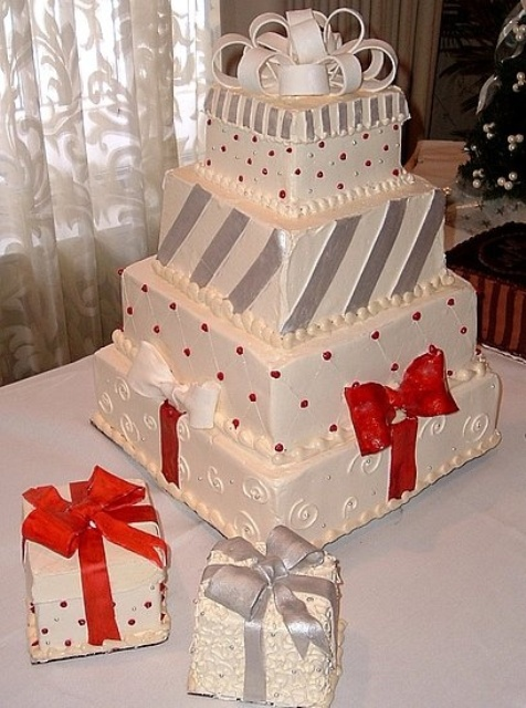 a Christmas wedding cake in red, white and silver composed as if it's made of gift boxes and topped with red bows