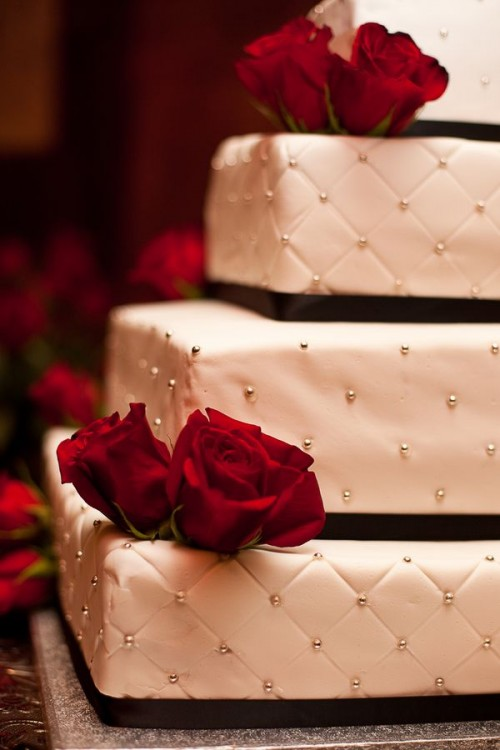 a refined Christmas wedding cake in white decorated with black ribbons and beads plus red roses is a cool idea for Christmas