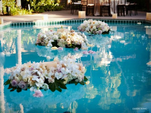 white and pink floral arrangements with greenery floating in the pool are a lovely and beautiful idea to style it for a wedding