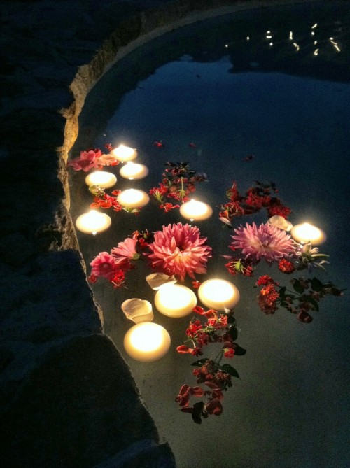 a pool with floating bright pink and red blooms and candles is a lovely idea to style the swimming pool for a wedding