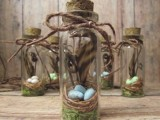 mini spring jars with nests, fake eggs, feathers, moss and rope for a natural spring wedding
