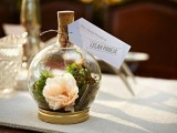 a mini terrarium with moss and blooms and some tags on it is a fresh, elegant and trendy idea