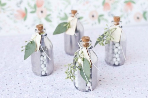 mini silver bottles with candies decorated with fresh greenery and leaves are cool spring wedding favors