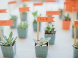 mini succulents in blue pots with bright markers are a cute sprign wedding favor idea that is fresh