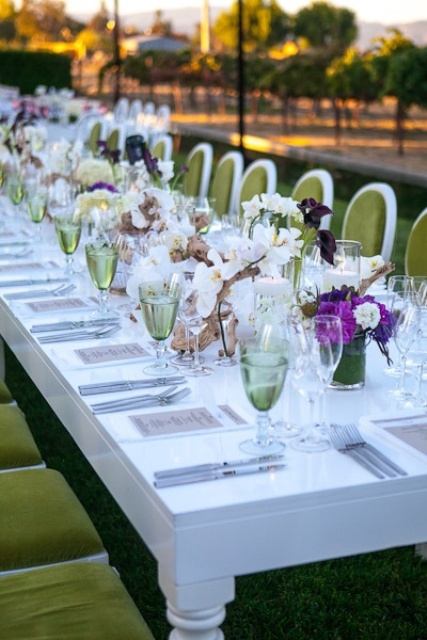 white, pink, purple and dark blooms in vases and some greenery for a bold look of your reception tables