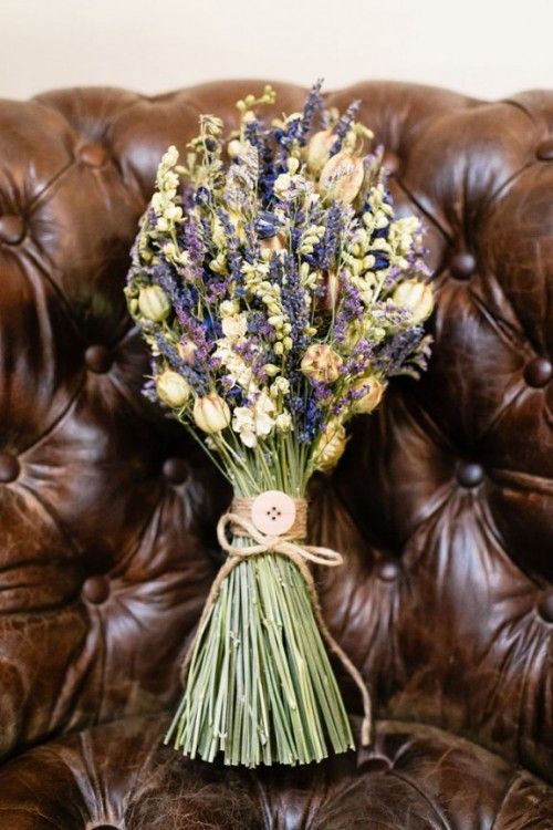 a wedding bouquet of dried blooms and grasses with yarn and a large button is a lovely idea for a summer or summer to fall wedding