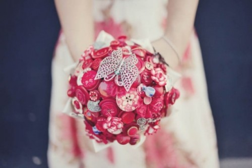 a red brooch and button wedding bouquet of buttons is a bright and cool idea that you can DIY