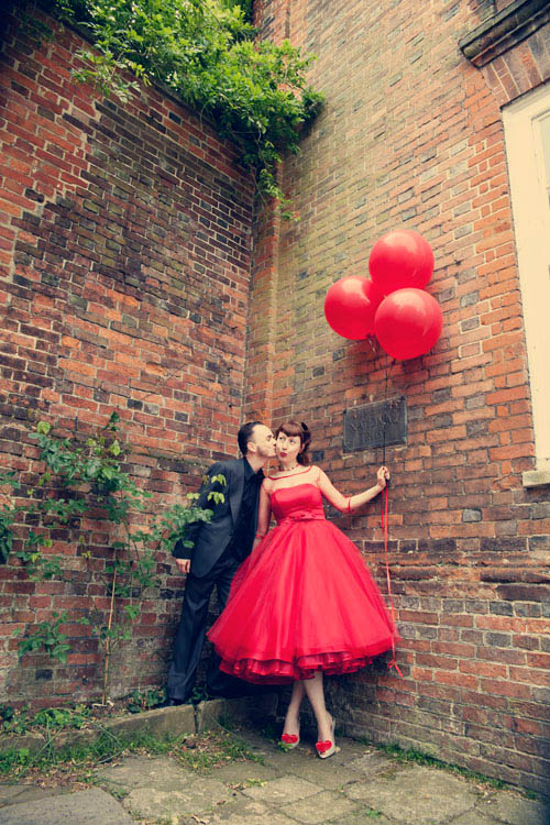 several red balloons instead of a traditional wedding bouquet are a fun and cool idea for a playful bride
