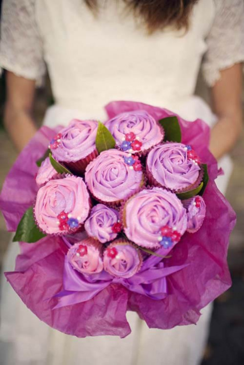 a purple cupcake wedding bouquet with some foliage and in a purple wrap is a very bold and cool idea for a sweet tooth