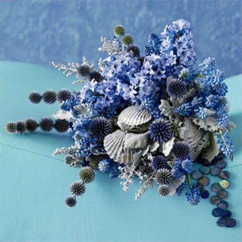 a coastal wedding bouquet of allium, blue flowers and seashells is an amazing idea for a coastal bride