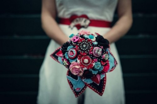 a colorful wedding bouquet of fabric, brooches and yarn balls in blue, red, pink and black is a very creative idea to rock