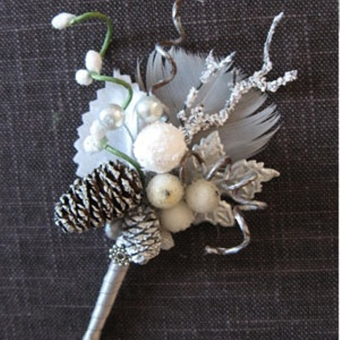 a sparkling winter wedding boutonniere with berries, beads, snowy pinecones, feathers, branches and shiny touches