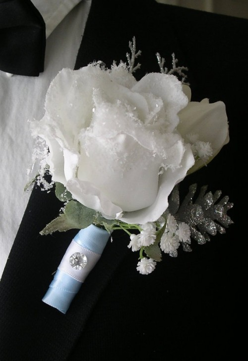 a shiny winter boutonniere with a glowing white rose, sparkling pinecones and some leaves