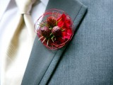a bright red boutonniere of petals, blooms and some red vine is a bold accent for a winter groom's look