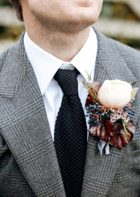 a winter wedding boutonniere with berries, little blooms and a large white peony rose, dark leaves and herbs
