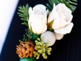 white roses, pinecones, berries, greenery and fir branches make up a stylish and chic winter wedding boutonniere