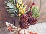 a rustic winter boutonniere with pinecones, berries, fir branches and printed ribbon in a bow for a winter groom