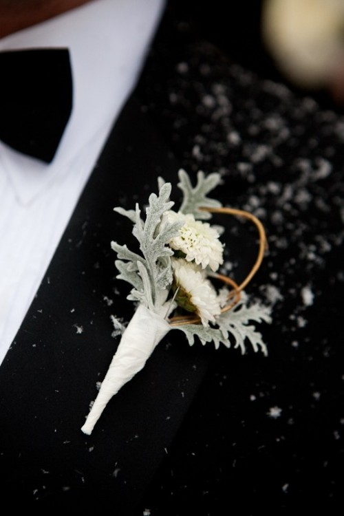 a pale boutonniere of white blooms and pale leaves for accessorizing a classic and chic groom's look