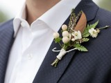 a relaxed winter wedding boutonniere of berries, greenery, white blooms and magnolia leaves looks elegant