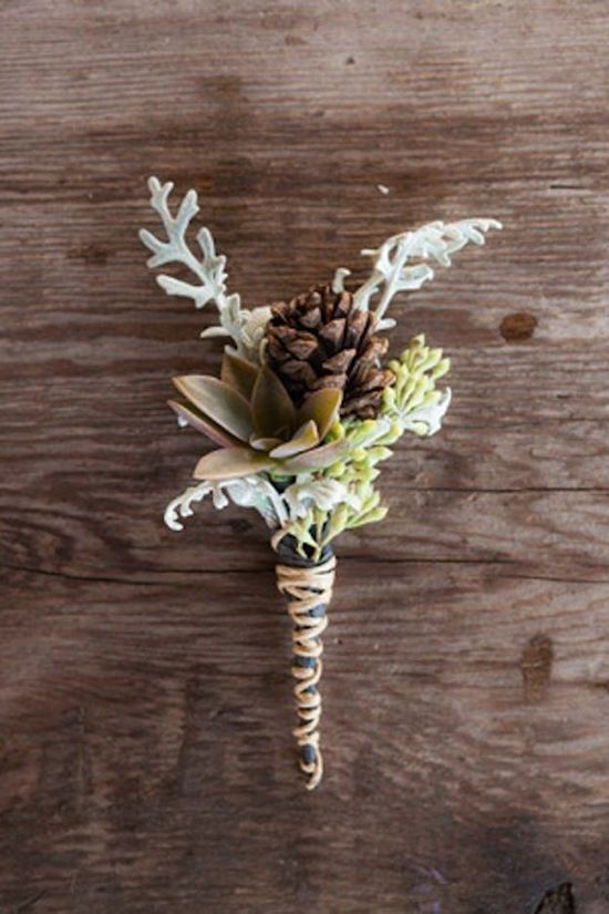 a rustic winter wedding boutonniere of greenery and pale leaves, pinecones and a succulents plus a twine wrap for a winter groom