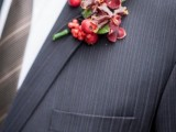 a red winter boutonniere of blooms, berries and leaves is a bold accent for a winter groom's look