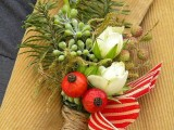 a bright boutonniere of red and white striped ribbons, berries, white blooms and greenery plus succulents for a winter groom