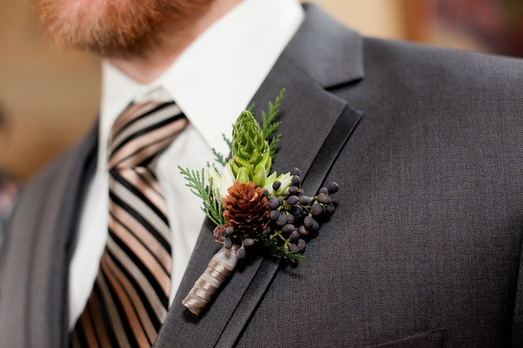 a white bloom, a pinecone, berries and greenery for accessorizing a winter groom's look and make it chic
