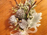 a pale winter wedding boutonniere with snowy pinecones, sitcks, berries and pale leaves plus a white ribbon bow